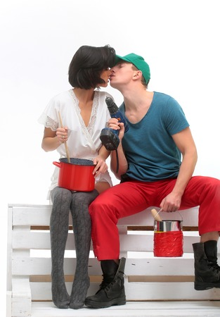 sexy household couple of pretty girl and handsome man with red pot, blue drill and paint bucket on wooden bench isolated on white background Stock Photo