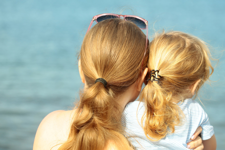 ponytails: Mother and son, beautiful woman and cute baby boy, with blond hair ponytails look at sea or ocean water on sunny summer day on blurred blue background Stock Photo