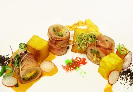 pancetta cubetti: Rolled ham or bacon with yellow red cubes served with vegetables and sauce on plate on white background. Modern molecular gastronomy Archivio Fotografico
