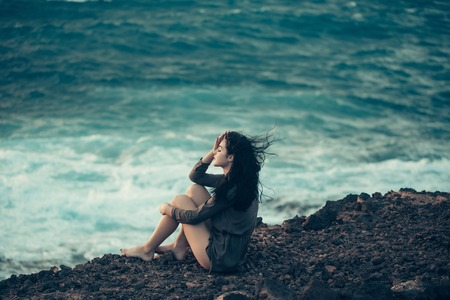 sexi: Pretty girl or beautiful woman, sexy slim brunette, sits on brown rocky surface on mountain slope on sunny summer day outdoors on blue stormy sea background