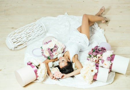 sexi: Sexy young pretty woman or cute smiling girl with long hair in white dress laying on bedsheet among lilac rose and peony flower boxes on wooden floor