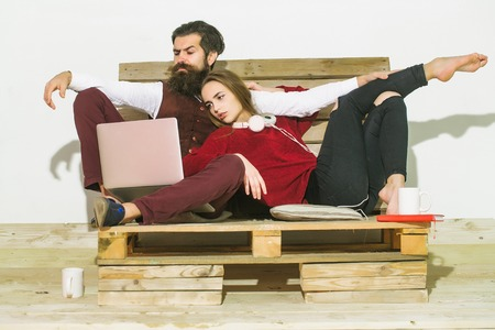 Young couple spend time together on wooden pallet sofa. Handsome man, bearded hipster with beard uses laptop, computer. Pretty girl or beautiful woman reads book
