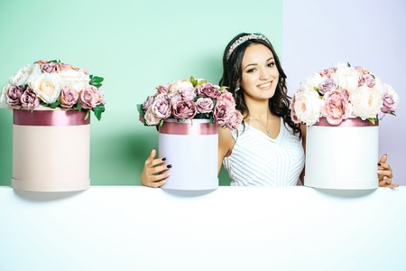 Sexy young pretty woman or cute smiling girl with crown on head, has long hair in white dress with lilac rose and peony flowers, bouquet boxes on green background