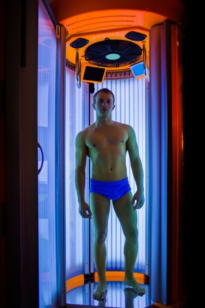muscle belly: muscular man with sexy healthy body standing in solarium spa salon in blue pants, has strong muscle on chest, belly and torso Stock Photo