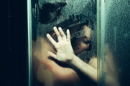 young couple of naked woman and man taking shower with water drops embracing in passion with wet bodies with hand on glass