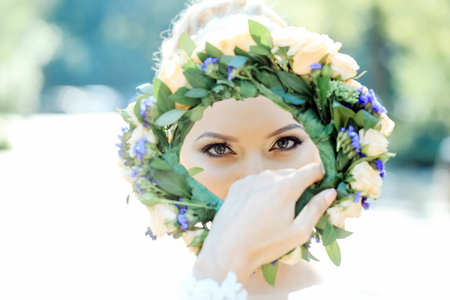 Pretty girl or beautiful woman with cute eyes looks through floral wreath of flowers and green leaves on sunny summer day outdoors on blurred background Stock Photo
