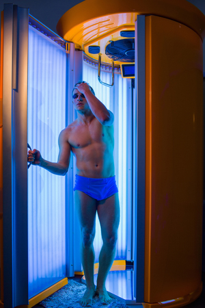 muscle belly: muscular man with sexy healthy body standing in solarium spa salon in blue pants and sunglasses, has strong muscle on chest, belly and torso