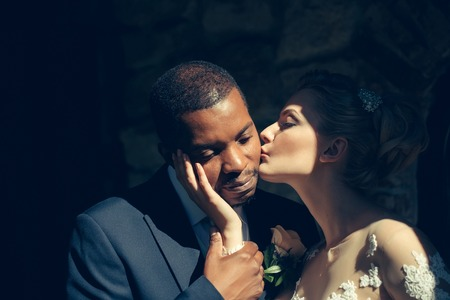 tenderly: Loving pretty girl or beautiful bride kissing tenderly handsome man or african American groom on sunny wedding day, married couple, outdoors on dark background