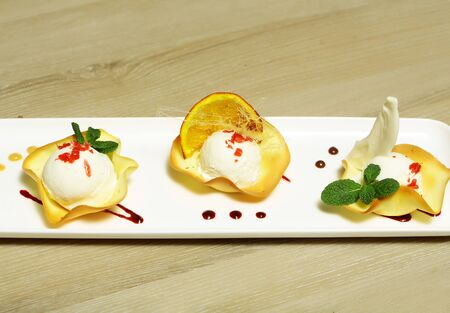Delicious ice cream balls in wafer cups garnished with caramelized sugar candy, orange and mint on rectangular plate on wooden background. Modern molecular gastronomy