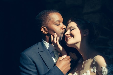 tenderly: Loving pretty girl or beautiful happy bride kissing tenderly handsome man or african American groom on sunny wedding day, married couple, outdoors on dark background