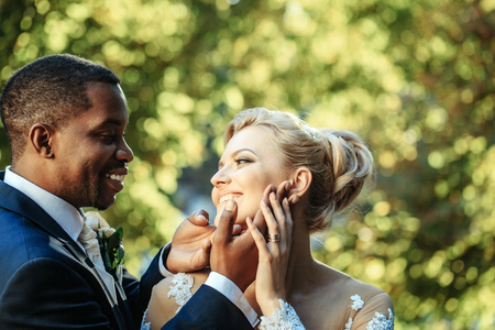 Loving groom or african American man gently touches face of pretty girl or adorable bride with beautiful make up and blond hair sunny summer day outdoors on blurred natural background