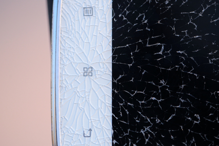 Brocken in pieces black glass of white mobile or cell phone as abstract background