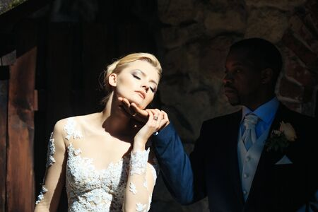 tenderly: Loving pretty girl or beautiful bride touching tenderly handsome man or african American groom on sunny wedding day, married couple, outdoors on dark background