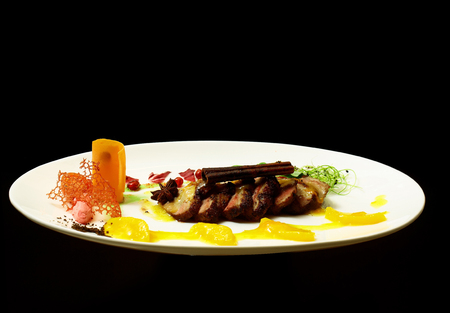 Roasted meat slices with cinnamon stick, spices, vegetables and yellow fruit jelly sauce on white plate isolated on black background. Modern molecular gastronomy