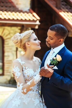 tenderly: Handsome man, african American groom hugging tenderly pretty girl or beautiful bride in white wedding dress, married couple, on sunny summer day outdoors on backyard background Stock Photo