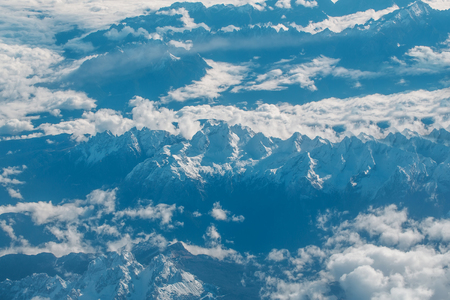 Idyllic snowy mountain peaks or tops under soft white clouds on grey rocky highland environment background. Overcast view from plane flight Stock Photo