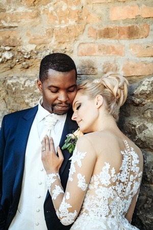 Loving couple of pretty girl or cute bride with beautiful blond hair in white sexy wedding dress and handsome man or african American groom outdoors on sunny day on brick wall background