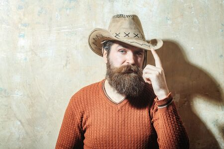cowboy beard: Bearded man, caucasian hipster, with long beard and moustache wearing cowboy hat and brown sweater poses with serious face on beige wall background, copy space Stock Photo