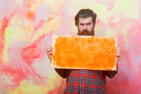 Serious bearded man, caucasian hipster, with long beard and moustache in red plaid shirt holding orange oil paint texture on canvas or board on abstract yellow and pink wall background, copy space