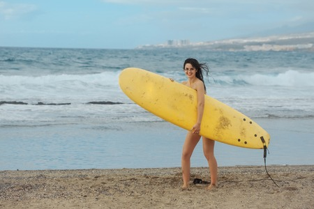 Pretty happy girl, surfer, or beautiful woman, sexy slim brunette, in sexi swimsuit with yellow surfboard on sandy beach outdoors on sunny summer day on blue sea background Stock Photo