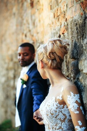 Handsome bearded man or african American groom in elegant suit coat with white tie and flower boutonniere for wedding ceremony looks at blurred bride on sunny day on brick wall background