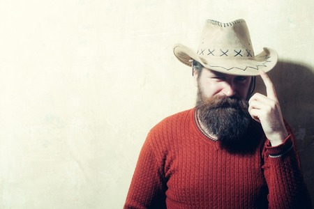 Bearded man, caucasian hipster, with long beard and moustache wearing cowboy hat and brown sweater poses with serious face on beige wall background, copy space Stock Photo
