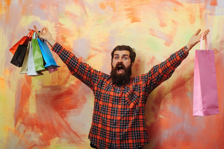 Happy bearded man, caucasian hipster, with long beard and moustache in red plaid shirt shouting with colorful paper shopping bags on abstract yellow and pink wall background