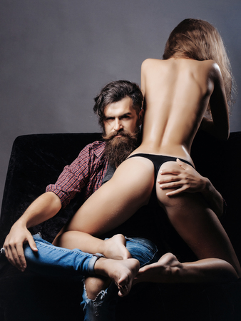 handsome bearded man with long beard on serious face sitting near young woman with sexy body legs and buttocks has bare back in lingerie. Stock Photo