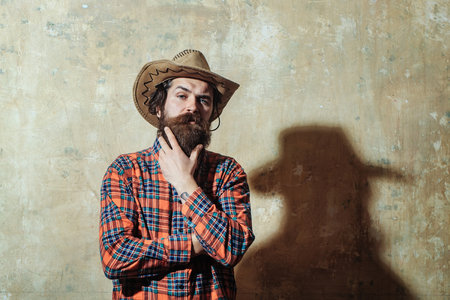 Bearded man, caucasian hipster, with long beard and moustache in cowboy hat and plaid shirt with serious face and black male shadow on beige grunge wall background Фото со стока