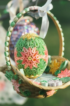Easter decor basket and egg decorated with colorful paper flowers in quilling technique on blurred background