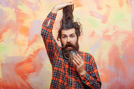 Bearded man, caucasian hipster, with long beard and moustache on surprised face holding stylish fringe hair, haircut, and metal mug or cup in red plaid shirt on abstract pink wall background Stock Photo