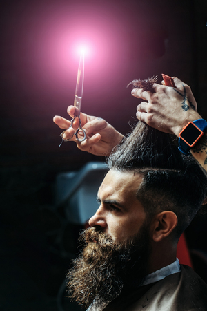 Bearded man with long beard, brutal, caucasian hipster with moustache, getting stylish hair cutting, haircut, with scissors and comb by hairdresser or barber with tattoo on hands at barbershop