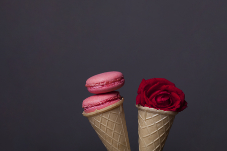 pink macaron, tasty cookies, biscuits or meringue in wafer or waffle ice cream cone on grey background with red rose flower, copy space