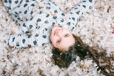 Śliczne szczęśliwy dziewczynka w piżamie leżące na podłodze pokryte puchem lub puchu i pierza, naturalnej, miękkiej, puszystej pióropuszem na teksturą tle