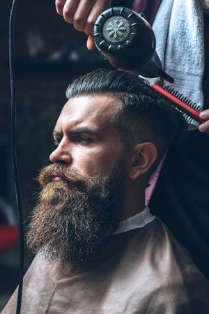 ブロー ドライヤーとくし理髪店で美容師によるヘアー スタイルを取得長いひげ、口ひげ、残忍な白人のヒップスターのひげを生やした男