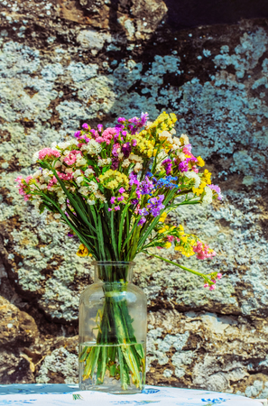 Beautiful colorful bunch of fresh, field, wild, blossoming flowers in bright summer colors in glass jar on sunny day on grey moss or lichen rock background Stock Photo