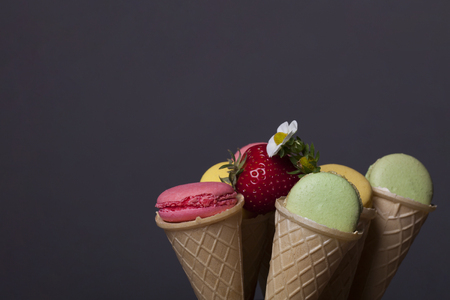 red strawberry fruit, colorful macaron, tasty cookies, biscuits or meringue in wafer or waffle ice cream cone, pastry pink, green, yellow color with flower on grey background, copy space