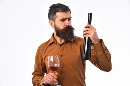 homme barbu, longue barbe, hipster caucasien brutal avec moustache tenant une bouteille de vin et un verre avec une boisson alcoolisée, a un visage sérieux, en chemise brune isolé sur fond blanc Banque d'images