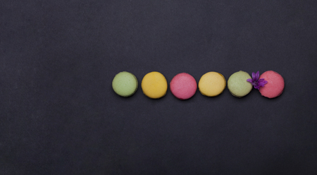 colorful macaron, tasty cookies, biscuits or meringue pastry pink, green, yellow color with calorie near violet spring flower on grey background, copy space