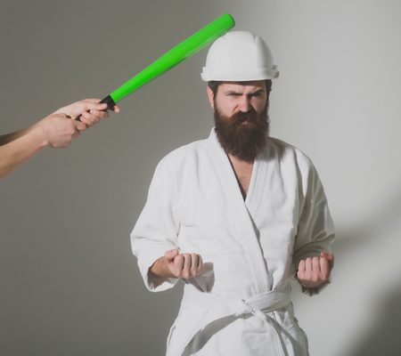 bearded karate man, long beard, brutal caucasian hipster with moustache in white kimono with black belt, builder helmet holds green baseball bat with angry face on grey background, unshaven guy