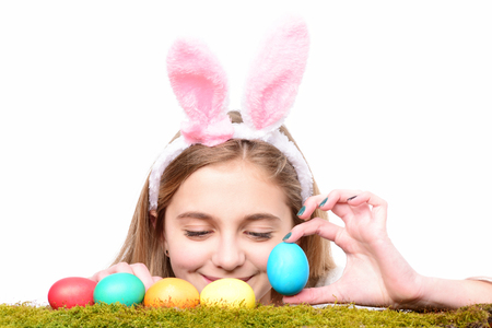 colorful painted easter eggs on green moss, traditional spring holiday food. happy girl in pink bunny ears with long blonde hair and surprised smiling cute face isolated on white background