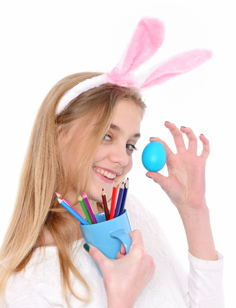 caras pintadas: happy easter girl painter with blue painted egg and colorful pencil set, has blond hair and smiling cute face in pink bunny ears isolated on white background. traditional spring holiday handmade food Foto de archivo
