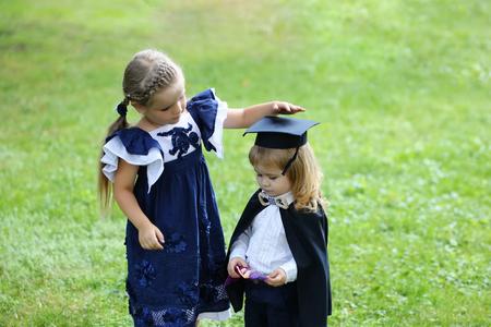 Roztomilá holčička s dlouhými vlasy v modrých šatech oblékání rozkošný malý chlapec v černém promoci klobouk nebo čepici a plášť v letní den venku na zelené trávě pozadí Automaticky přeloženo z angličtiny. Zobrazit původní text Původní text.