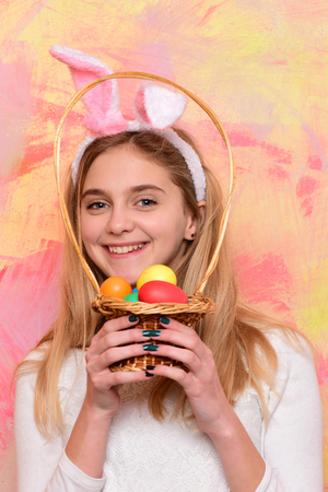 happy girl in pink bunny ears with colorful painted easter eggs in basket, has smiling adorable face and long blonde hair on abstract background. traditional spring holiday food