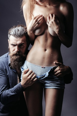 bearded handsome man and female slim flexible body of young pretty sexy woman or girl topless with bare belly and chest in jeans shorts Stock Photo