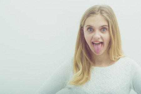 Pretty girl or cute smiling young woman with blond hair and adorable happy face in white sweater, blouse or sweatshirt showing tongue on grey background, copy space