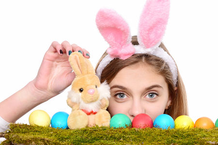 happy easter girl in pink bunny ears with cute face with colorful painted eggs on green moss and rabbit toy, isolated on white background. traditional spring holiday food