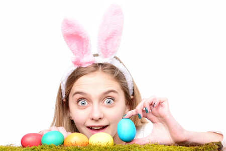 happy easter celebration and decoration. traditional spring holiday food. girl in pink bunny ears, colorful painted eggs on green moss, long blonde hair, surprised face isolated on white background Stock Photo