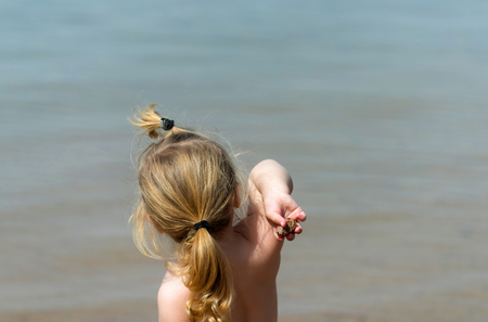 Cute baby boy or girl, small, little child with long blond hair, throwing stones, pebbles in blue sea, ocean water on sunny summer outdoor on seascape background. childhood, happiness and vacation