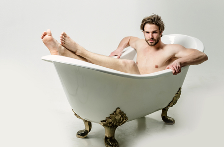 Handsome man or unshaven caucasian macho with stylish haircut, hair, with naked, sexy muscular torso and arms with biceps, triceps sitting in classic bath, tub barefoot on white background